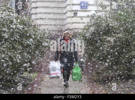 Moskau, Russland. 9. Oktober 2015. Eine Frau Tragetaschen während eines Schneefalls. © Sergei Bobylew/TASS/Alamy - Stockfoto