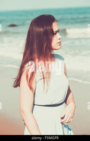 Historische junge Frau am Strand trägt ein blaues Kleid - Stockfoto
