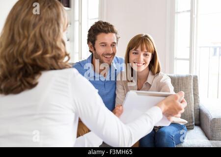 Architekt präsentiert ein neues Projekt auf digital-Tablette, ein fröhliches junges Paar im Büro - Stockfoto
