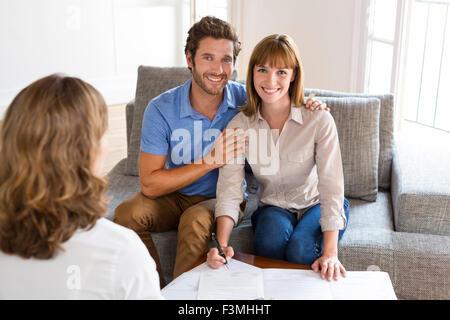 Junges Paar Besitzer Immobilienmakler für Haus-Investition zu treffen. Unterzeichnung eines Vertrages. Gesicht-Kamera - Stockfoto
