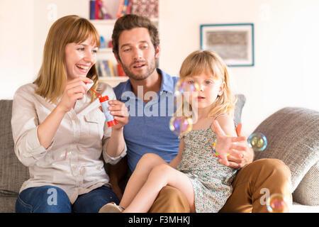 Fröhliche Eltern und Tochter Seifenblasen zu Hause auf sofa - Stockfoto