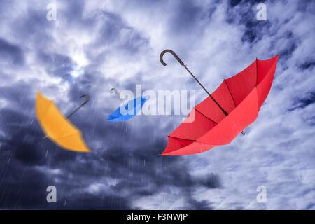 Fliegende Regenschirme im Himmel mit Niederschlägen - Stockfoto