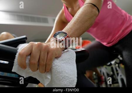 Nahaufnahme einer Frau mit einem tragbaren Polar-Aktivitäts-Anzeige während eine Spinning-Kurs - Stockfoto