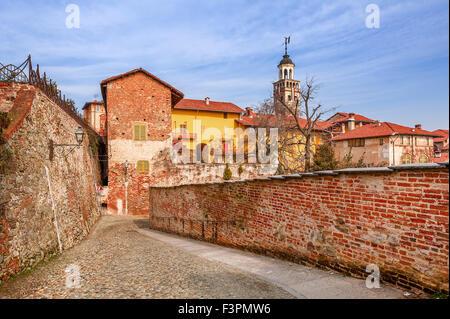 Kopfsteinpflaster, roten Backsteinmauer und bunten Häuser in der alten Stadt von Saluzzo im Piemont, Norditalien. - Stockfoto