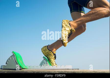 Sportler tragen gold Laufschuhe zieht in einer Unschärfe von aus den Startlöchern Race track - Stockfoto
