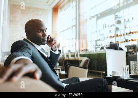 Afrikanischen Geschäftsmann telefonieren mit Handy während der Wartezeit in einer Hotel-Lobby. Junger Geschäftsmann - Stockfoto