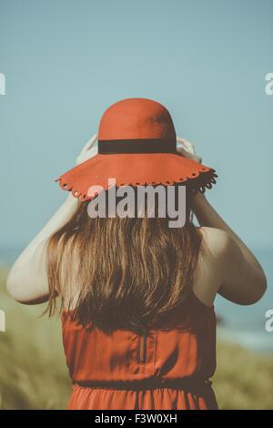 Junge Frau in einem roten Kleid am Strand - Stockfoto