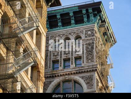 Aufbau der Fassade mit Terrakotta-Ornament, Kupfer Gesims und Feuerleitern in Soho, Broome Street, Manhattan, New - Stockfoto