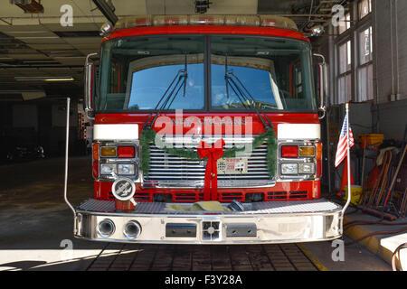 Feuerwehrauto, verziert mit Grün Christmas Garland und festlichen roten samt Bögen im Feuerwehrhaus, neu Orleans, - Stockfoto