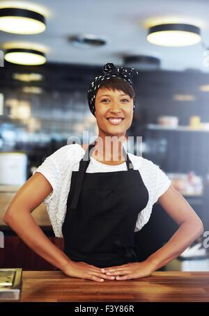 Sicher erfolgreiche junge Kleinunternehmer stehen hinter der Theke in ihrem Café geben der Kamera eine glückliche - Stockfoto