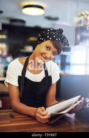 Lächelnden jungen Coffee house Eigentümer steht hinter der Theke in einer Schürze lehnte sich nach vorne, um das - Stockfoto