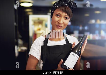 Attraktive junge afroamerikanische Dame in eine Schürze präsentiert eine Flasche Rotwein an einem Kunden in ein - Stockfoto