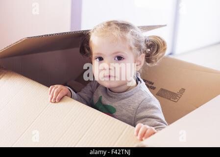Kleine Mädchen spielen im Karton, Porträt - Stockfoto
