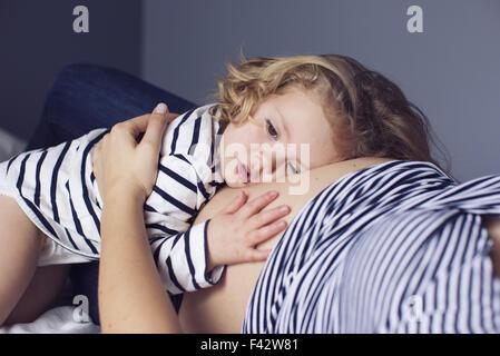 Kleine Mädchen ihren Kopf und Ihre Hand auf Mutters schwangeren Bauch ruht - Stockfoto