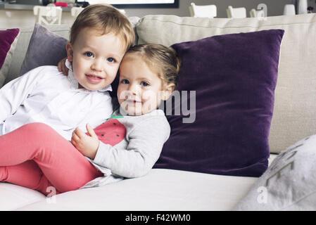 Junge Geschwister sitzen zusammen auf Sofa, Porträt - Stockfoto