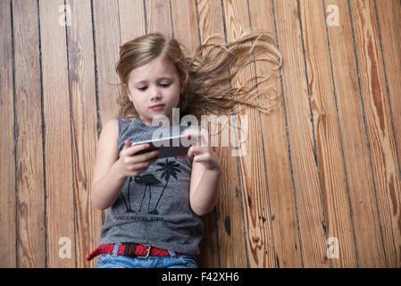 Kleines Mädchen auf Boden mit smartphone - Stockfoto