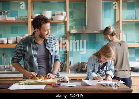 Junge Tochter Zeichnung Ar Küchentheke während Eltern Mahlzeit zubereiten - Stockfoto