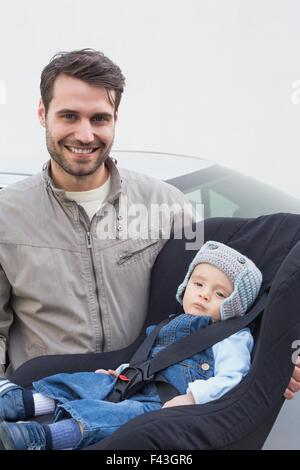 Vater mit Baby in seinem Autositz - Stockfoto