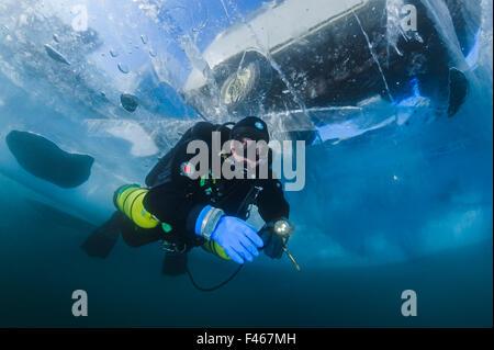 Taucher schwimmt unter transparente Eis (1m dick) mit Minivan oben sichtbar. Baikalsee, Russland, März 2012. -Modell - Stockfoto