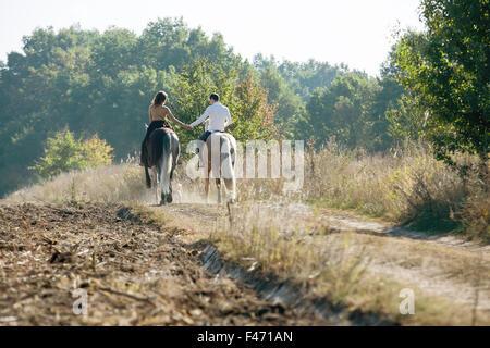 Junges Paar in Liebe auf einem Pferd - Stockfoto