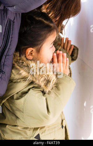 Seitenansicht eines jungen japanischen Kind, Mädchen, 3-4 Jahre, mit dicken Wintermantel, gefalteten Händen vor - Stockfoto