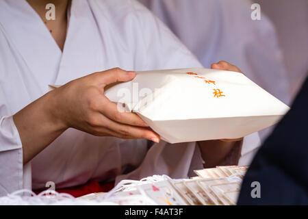 Nishinomiya Schrein, Japan während Shogatsu, ja. Miko, Schrein Mädchen Übergabe engimono Paket an der Theke, um - Stockfoto