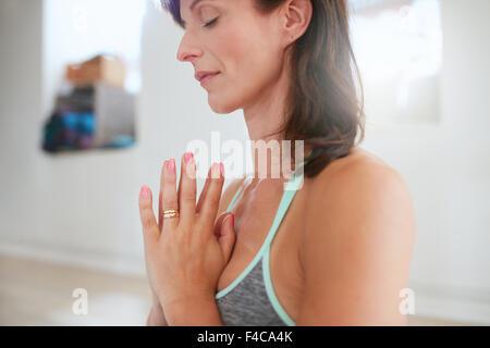 Frau mit Händen zusammen meditieren. Schuss von Reife Frau beim Yoga hautnah. - Stockfoto