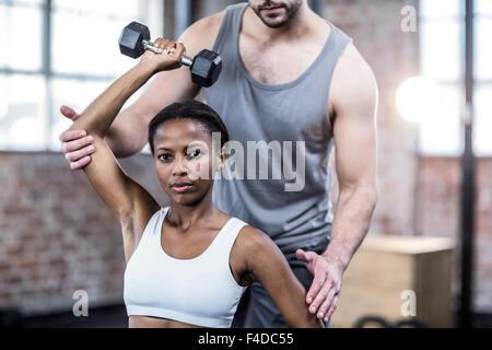 Persönlicher Trainer arbeiten mit Klienten mit Hantel - Stockfoto