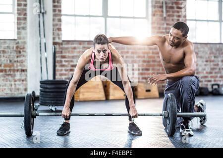 Trainer helfen Frau mit Hantel heben - Stockfoto