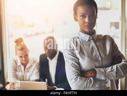 Erfolgreiche junge schwarze Geschäftsfrau vor Multi ethnischen Gruppe von Menschen - Stockfoto