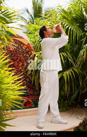 Ein Junge mexikanischer Mann bläst eine Muschelschale um den Beginn der Temazcal Behandlung im Spa Aqua Live Aqua - Stockfoto