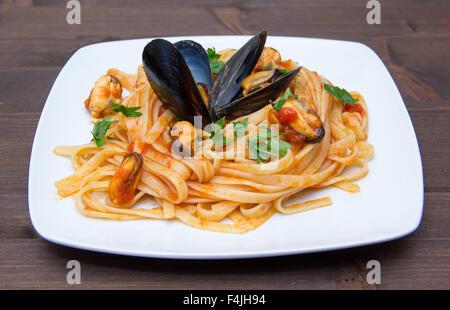Pasta mit Muscheln auf dem Teller auf Holztisch - Stockfoto