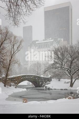 Schneefall am Central Park-Gapstow-Brücke und den Teich. Ruhigen Winterlandschaft mit Blick auf die Wolkenkratzer - Stockfoto
