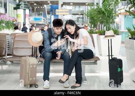 Junge asiatische paar mit Smartphone beim Sitzen im Flughafen-Terminal für das Boarding warten. - Stockfoto