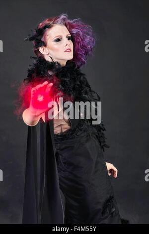 Spuk, schwarzäugige Hexe, Gießen magischen rote Energie aus einer hand - Stockfoto