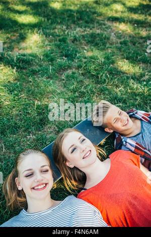 Drei glückliche Teenager Freunde auf Skateboard in der Wiese liegend - Stockfoto