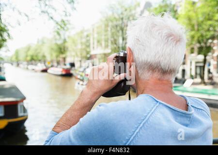 Niederlande, Amsterdam, senior woman eine Aufnahme mit analogen Kamera bei Stadtgracht - Stockfoto
