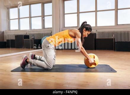 Junge Frau mit Wasserkocher Glocke im Fitnessstudio trainieren. Fitness weibliches Modell Crossfit Training im Fitnessstudio - Stockfoto