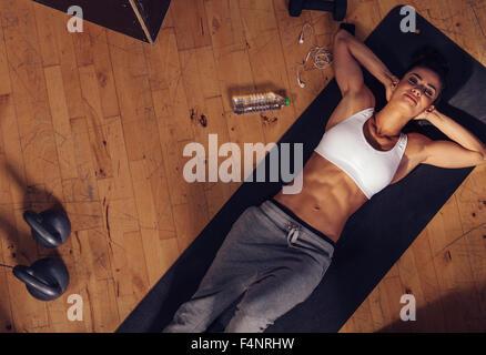 Draufsicht der entspannenden junge Frau, die auf Fitness-Matte liegen. Overhead Schuss Sportlerin, ruhen Sie sich - Stockfoto