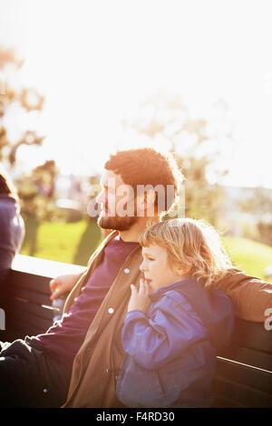 Schweden, Skane, Malmö, Vastra Hamnen, Vater und Sohn (6-7) auf Parkbank in der Sonne sitzen - Stockfoto