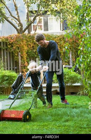 Schweden, Skane, Osterlen, Borrby, Vater und Sohn (4-5) Rasenmähen im heimischen Garten - Stockfoto