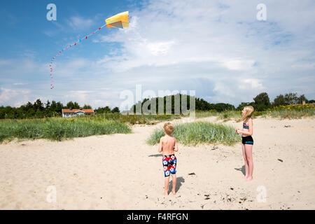 Schweden, Skane, Vejbystrand, junge (6-7) und Mädchen (10-11) fliegende Drachen - Stockfoto