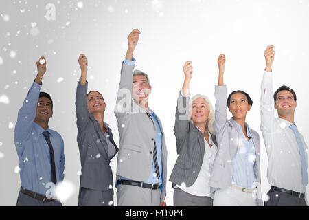 Zusammengesetztes Bild des Lächelns Geschäftsleute Hände erhebend - Stockfoto