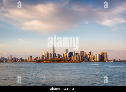 New Yorker Wolkenkratzer und Lower Manhattan Financial District im Abendlicht mit Battery Park und Ellis Island. - Stockfoto