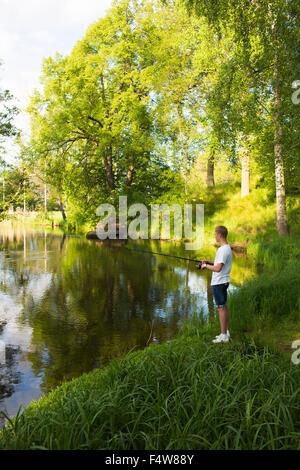Schweden, Ostergotland, Mjolby, junge Mann Angeln im Fluss Svartan - Stockfoto