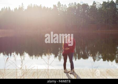 Schweden, Ostergotland, Mjolby, paar umarmt am Steg am Skogssjon See - Stockfoto