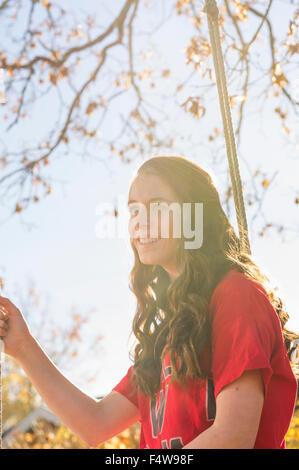 Schweden, Sodermanland, Stigtomta, Teenage Mädchen (14-15) sitzen auf Baum schwingen im Sonnenlicht - Stockfoto