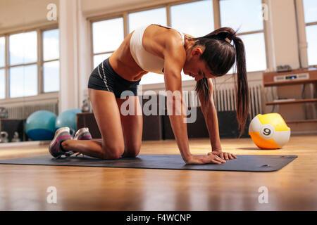 Aufnahme der jungen Frau den Rücken dehnen. Muskulöse Frau auf Fitness-Matte im Fitness-Studio trainieren. - Stockfoto