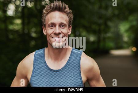 Lächelnd hübschen muskulöseren jungen Mann stehend im Freien in einem bewaldeten Park Sportbekleidung Blick auf - Stockfoto