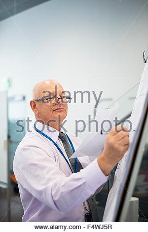 Geschäftsmann am Whiteboard schreiben - Stockfoto